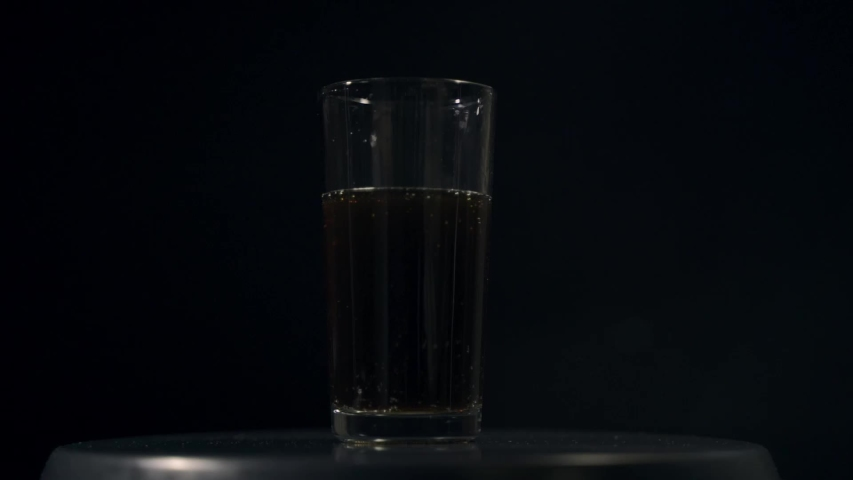 Cold cola with ice in a tall transparent glass | Shutterstock HD Video #1046405296