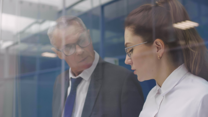 Businessman talks to his younger female assistant. Office colleagues communicate. View through transparent glass window | Shutterstock HD Video #1046535136
