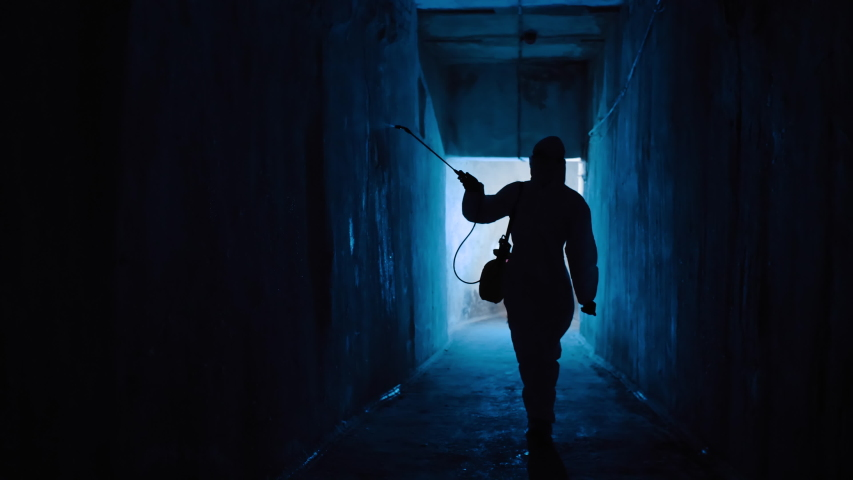 Silhouette of man in protective suit in dark tunnel sprays disinfectant liquid on walls. Virologist in hazmat disinfects room from bacteria and diseases, coronavirus prevention, epidemic, USA, Italy | Shutterstock HD Video #1046537566