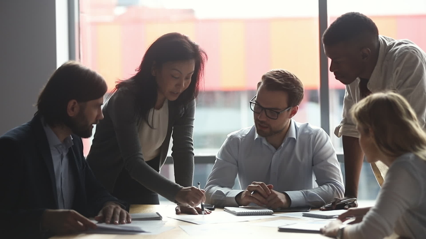 Motivated middle aged asian female team leader explaining company development strategy to smiling young diverse colleagues. Happy multiracial business people enjoying working together at office.   Shutterstock HD Video #1046595526