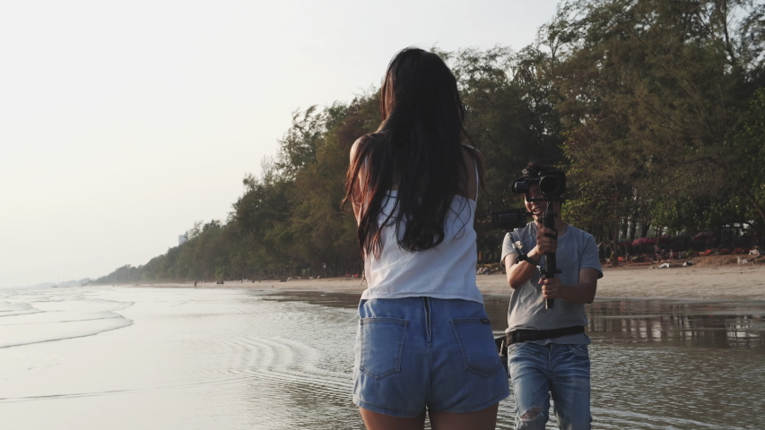Backstage of the sexy asian young girl running away from freelance paparazzi at seaside beach summer season. 4K Slow motion. Concept of fashion magazine, news reporter, technology and paparazzi photo. | Shutterstock HD Video #1046613946