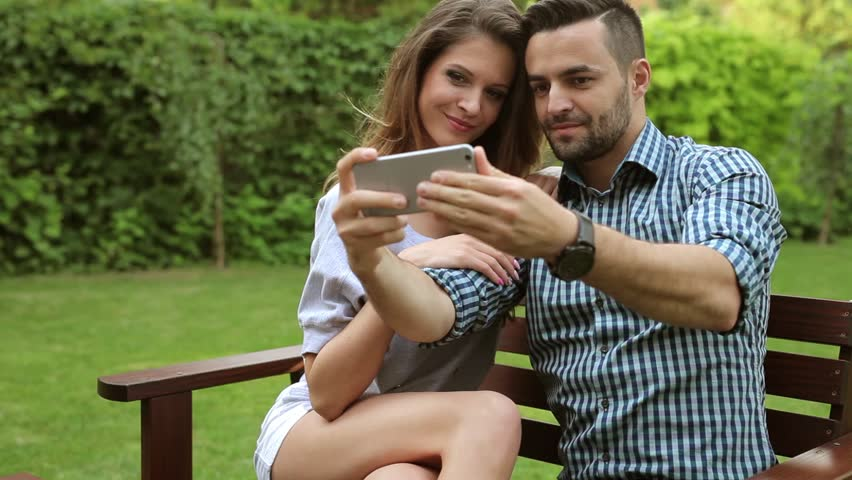 Coupl sitting on the bench and taking selfie picture. They are kissing