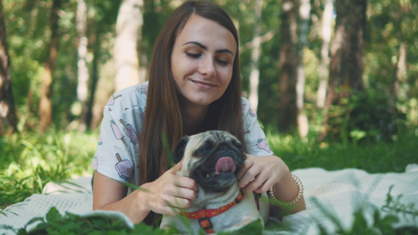 Smiling lady is taking free time with her dog. Woman relaxing in the nature with her little pug dog. Close up. Copy space. 4K. | Shutterstock HD Video #1046771086