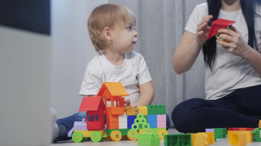 Childhood happy family mom and children are playing concept little girl and boy brother and sister collects constructor teamwork. child plays toys sitting on floor. children play in team toys on floor | Shutterstock HD Video #1046814886