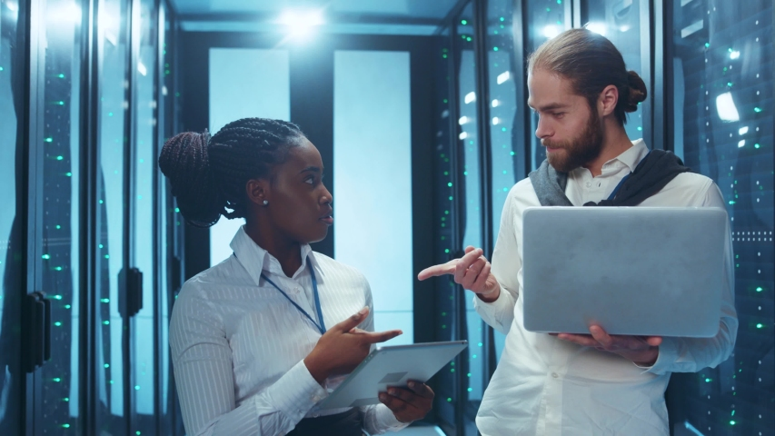 Fun multi-racial team of data center using app on digital tablet pointing fingers at camera and laughing hard. Operational server racks on background.   Shutterstock HD Video #1046828416