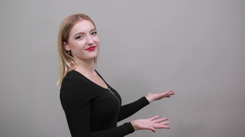 Young blonde girl in black jacket on grey background happy woman smiles and points the direction with her index finger, demonstrates something | Shutterstock HD Video #1046846146