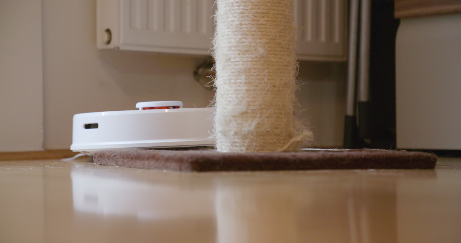 Robot cleaner cleans the room. Smart home. Robot vacuum cleaner performs automatic cleaning of the apartment at a certain time.  | Shutterstock HD Video #1046906566