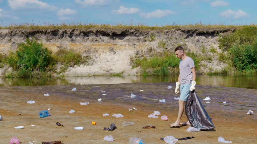 Man in a gray t-shirt and denim shorts is collects plastic trash on the banks of a dry and polluted river or lake and listens to music on earphones. Ecological catastrophy. Anthropogenic influence. 4K | Shutterstock HD Video #1046929516