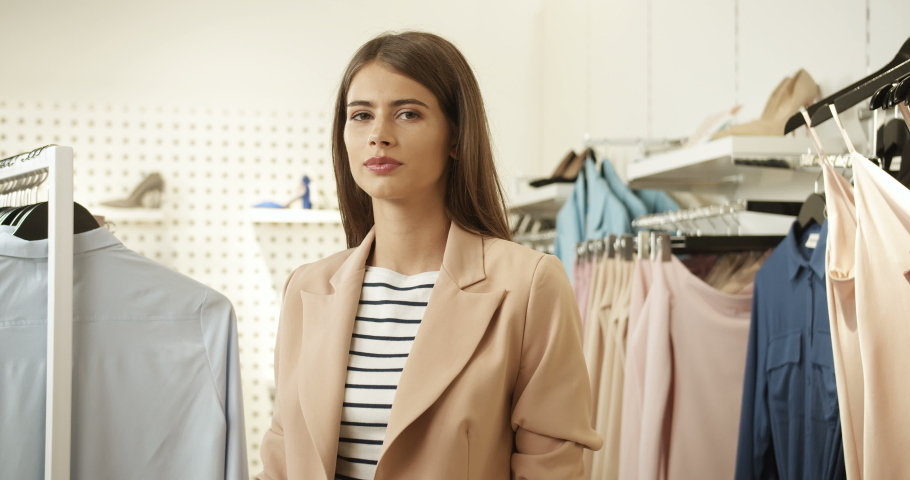 Portrait of young pretty happy woman smiling cheerfully to camera in clothing shop. Close up of beautiful Caucasian girl posing while standing in fancy store. Female fashion buyer. | Shutterstock HD Video #1046966266