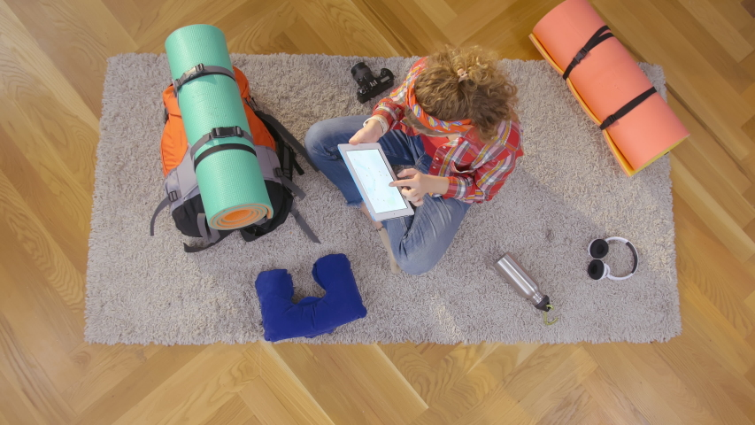 Top view of young female traveler using digital tablet checking route sitting on floor and packing hiking equipment preparing for summer travel outdoors. | Shutterstock HD Video #1046968876