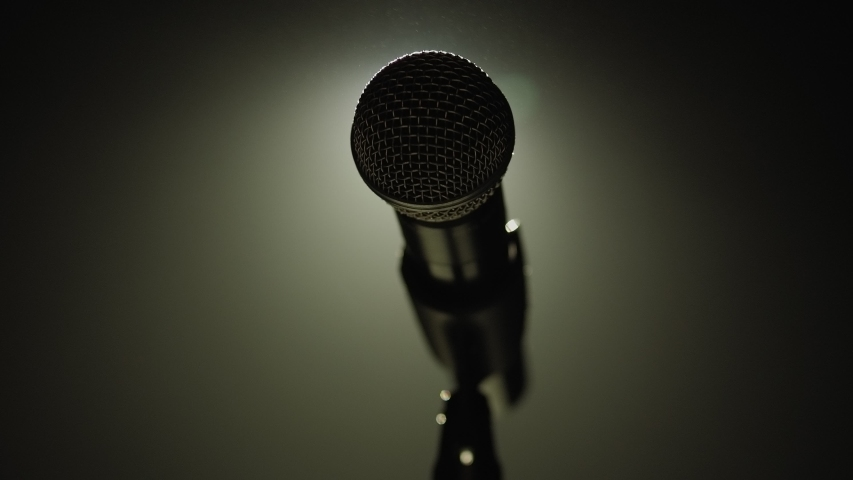 Close-up of microphone on stage against a black background with white lighting and smoke. The silhouette of the microphone in the dark. Music instrument concept. | Shutterstock HD Video #1046972356