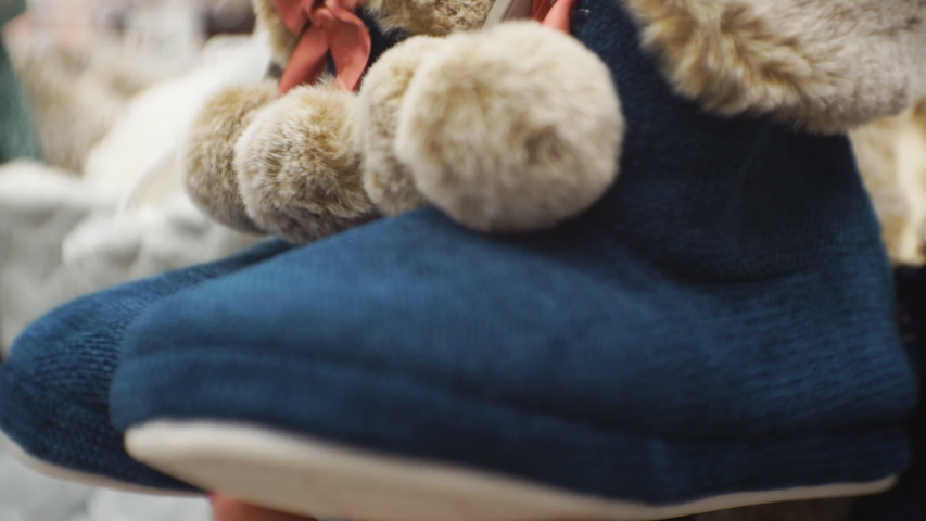 A woman checks the quality of the goods in the store. A woman holds soft slippers in her hands, checking their quality. | Shutterstock HD Video #1046986306