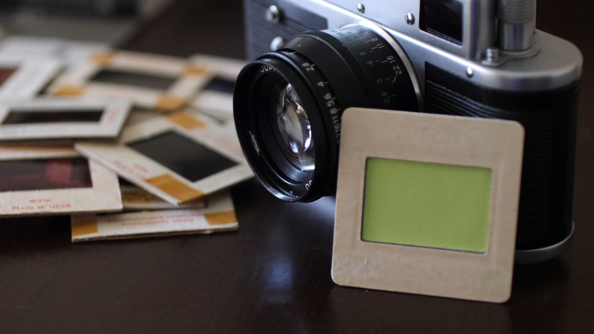 Vintage film camera and slide film with green screen | Shutterstock HD Video #1046997316