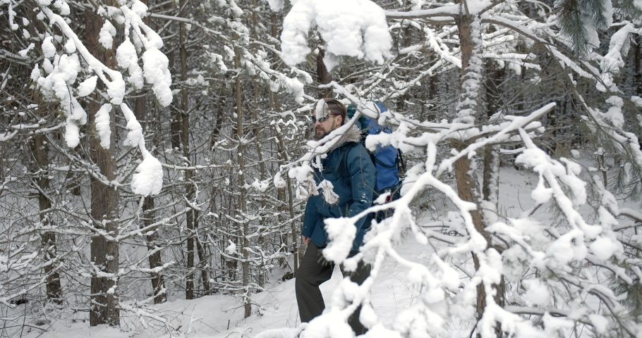 Male bearded tourist in winter clothing carrying on big backpack while walking on snowy coniferous forest. Concept of travelling adventure and natural landscape | Shutterstock HD Video #1047009406