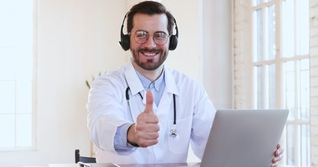 Friendly smiling professional male medic doctor in headset makes conference video call on laptop  consult patient look at camera, shows thumbs up recommend telemedicine online chat service app concept