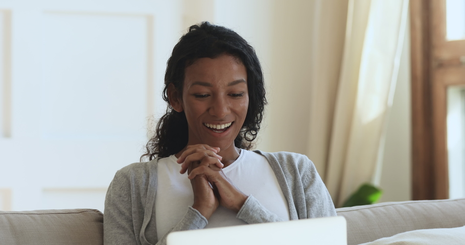Head shot amazed millennial african american woman looking at laptop screen, reading email with good news. Happy excited young biracial girl surprised by unbelievable success, winner notification. | Shutterstock HD Video #1047056836
