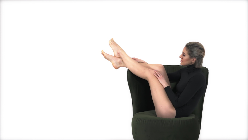 Fitness model in black sportswear leotard relaxing on armchair and touching her leg gently. Fashion and sport concept | Shutterstock HD Video #1047198316