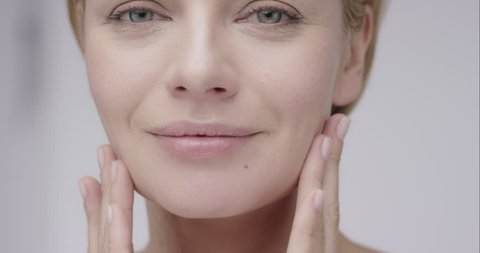 Close up of Beautiful healthy woman touching smooth skin on face in slow motion for beauty skincare concept on a grey background Shot in 6K on RED EPIC DRAGON