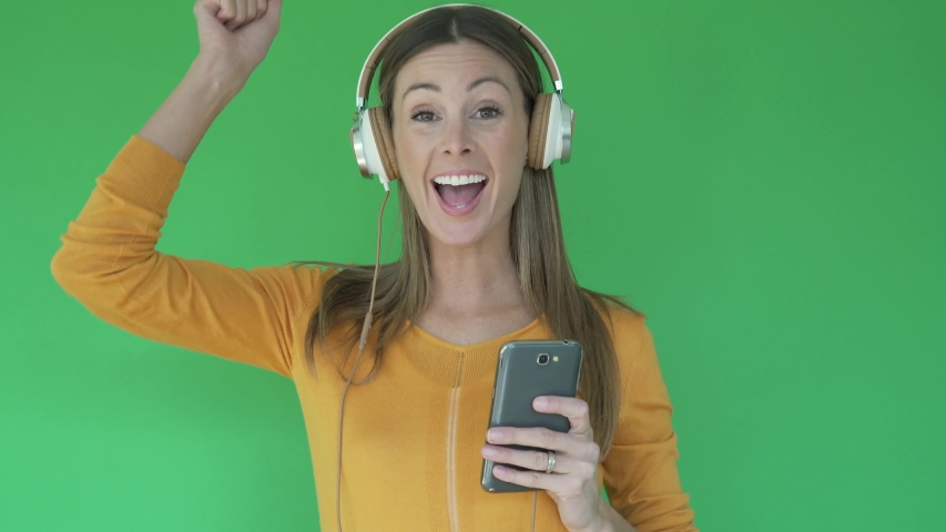 Woman on green background listening to music with headset | Shutterstock HD Video #1047332626