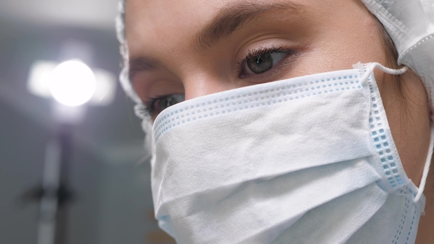 Girl surgeon doctor in surgical mask looks down at patient and then to side at monitor or assistants. Operation, practitioner, operating room, surgery, transplantation, medicine concept. Close-up | Shutterstock HD Video #1047515746