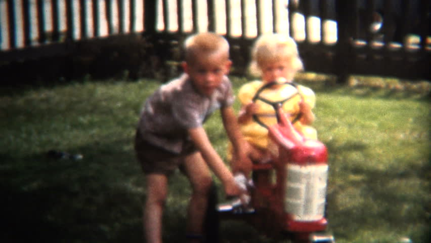 IOWA, USA - JULY 1954: Brother pushing sister around in the front yard while steering the toy tractor.