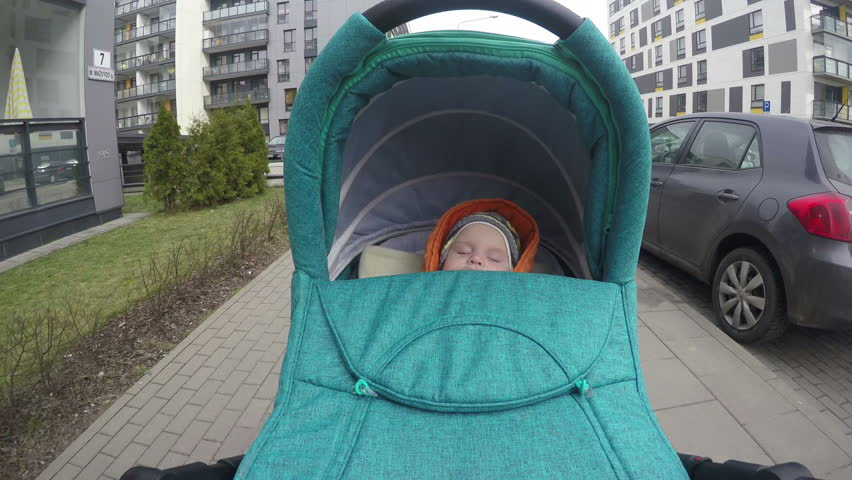 Newborn baby girl sleep in her pushchair stroller cradle while walking between cars and flat houses in living district. Wide angle POV shot. 4K UHD. | Shutterstock HD Video #10477727