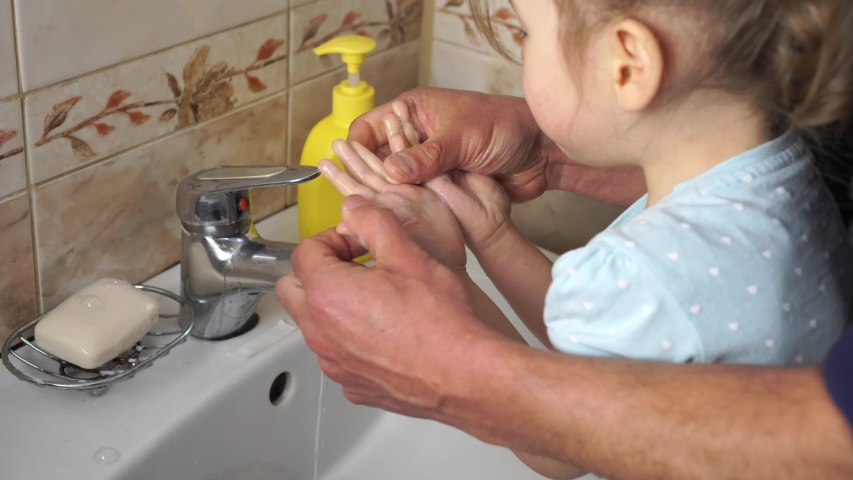 Protection against coronavirus (COVID-19). Dad washes a small child's hands with soap over the sink with running water. Personal hygiene | Shutterstock HD Video #1048482256