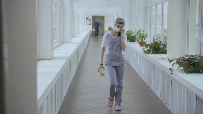 Masked doctor walks down corridor with tests at Russian hospital quarantine | Shutterstock HD Video #1048598356