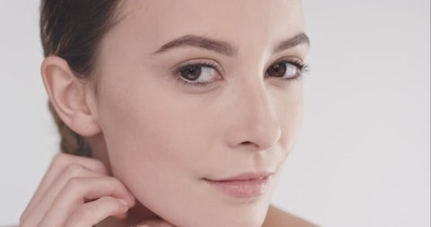Close up beauty portrait of beautiful woman touching face in slow motion skincare concept shot against grey background shot in 6K Red Epic Dragon