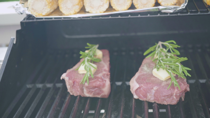 Grilling New York steak with a slice of butter and rosemary on an outdoor gas grill. | Shutterstock HD Video #1048864186