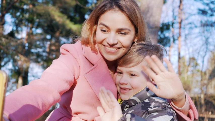 Beautiful mother and son having a phone video call. Attractive family taking selfies outdoor in the park. Happy family concept.    Shutterstock HD Video #1048928476