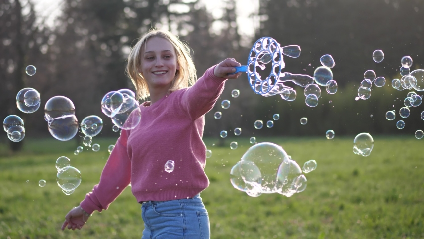 Happy Woman Making Bubbles in the Nature at Sunset   Shutterstock HD Video #1049074636