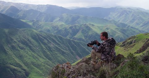 Photographer in the Mountains. Photographer takes pictures of wildlife in the background spectacular views of the mountain gorge