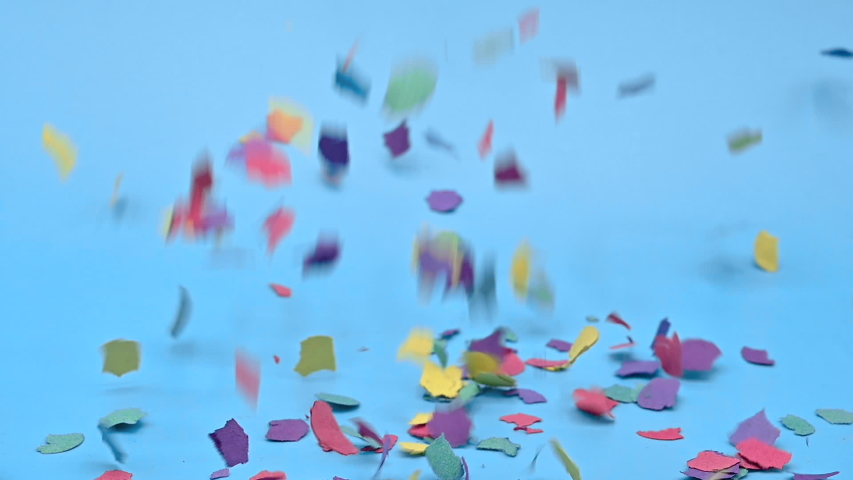 Real multi-colored confetti falling on blue background . | Shutterstock HD Video #1049540056