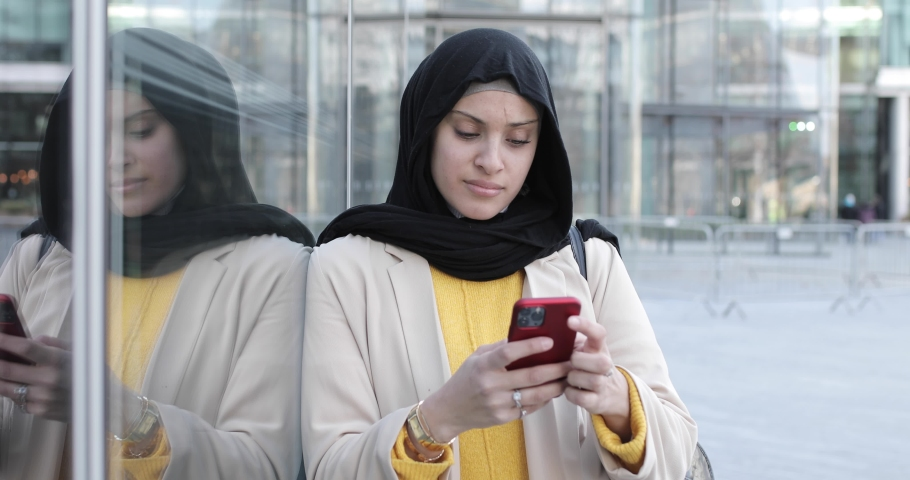 Smiling woman wearing hijab and using smartphone | Shutterstock HD Video #1049571496