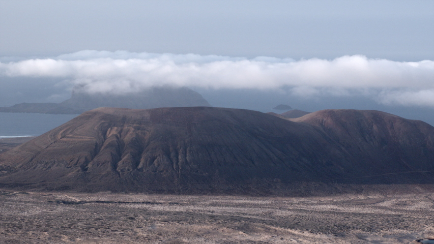Clouds passing over the volcanic peaks of La Graciosa, an island in the Canaries. | Shutterstock HD Video #1049612656