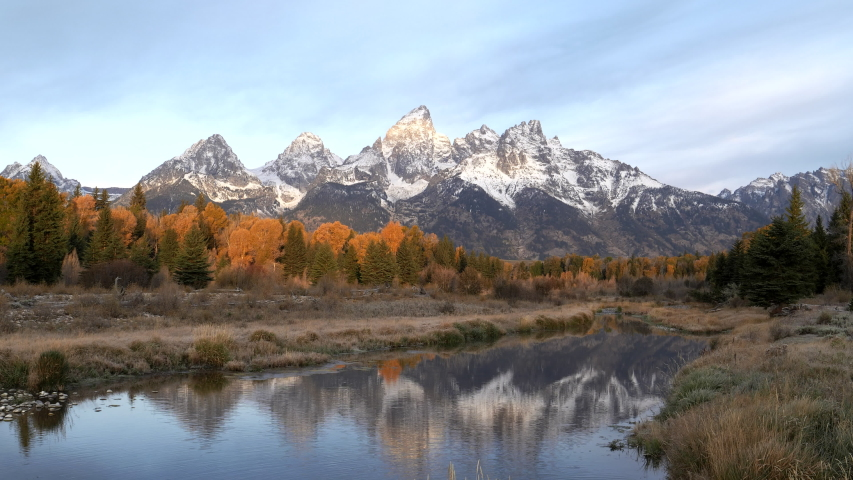 Autumn morning clip of the snow covered teton mountains reflected in calm water at schwabachers landing of grand tetons national park, wyoming | Shutterstock HD Video #1049633716