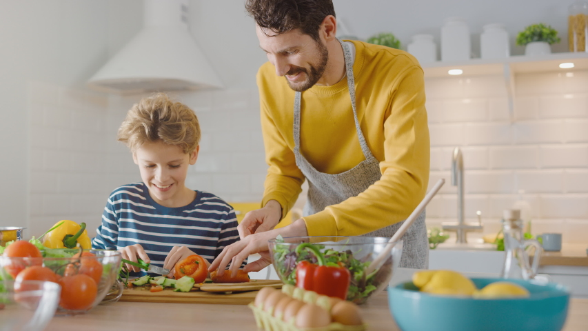 In the Kitchen: Father and Cute Little Son Cooking Together Healthy Dinner. Dad Teaches Little Boy Healthy Habits and how to Cut Vegetables for the Salad. Happy Child and Parent Spend Time Together | Shutterstock HD Video #1049665486