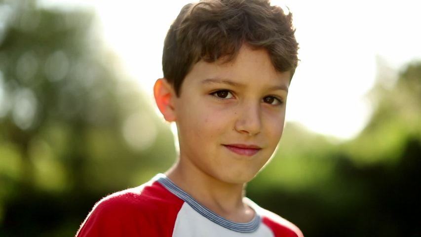 Attractive handsome child young boy portrait outside with lens-flare sunshine | Shutterstock HD Video #1049719096