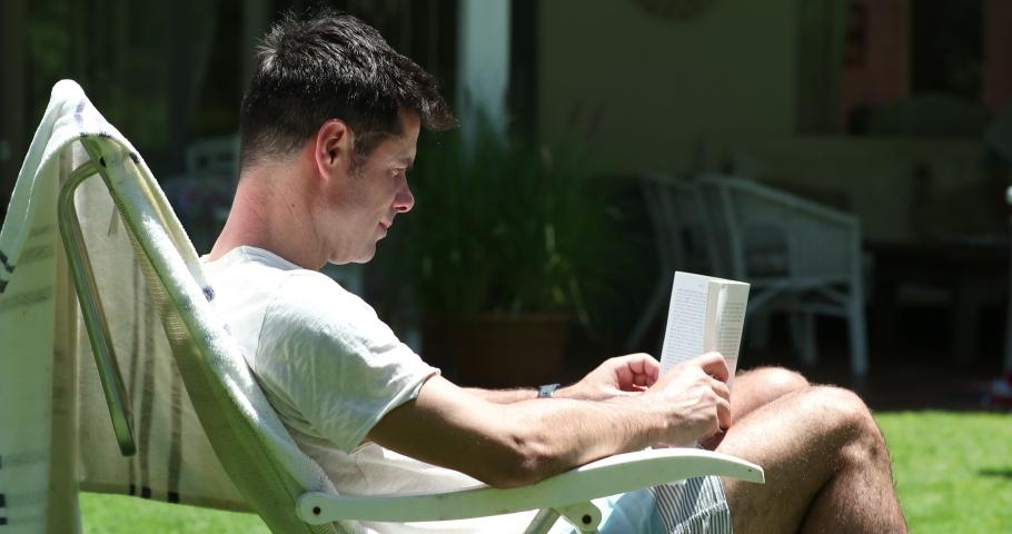 Candid man reading book novel story outside in backyard home | Shutterstock HD Video #1049719186