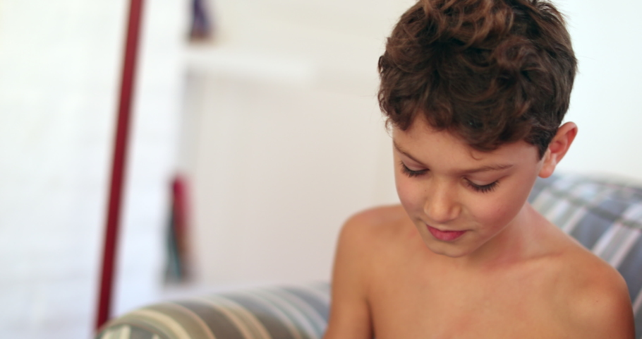 Candid kid using tablet sitted on sofa playing game | Shutterstock HD Video #1049719516