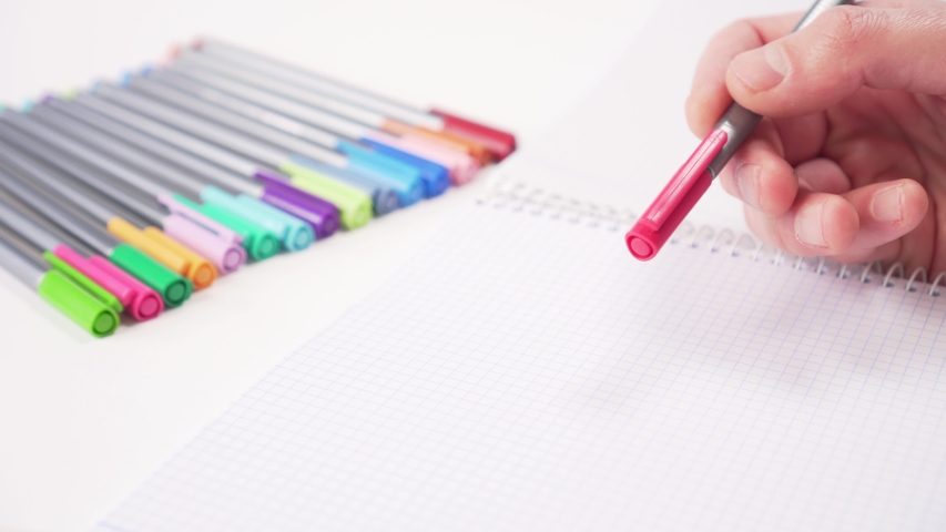 Multi-colored pens on a white table. Hand is preparing one red for use. School supplies for creativity | Shutterstock HD Video #1049738146