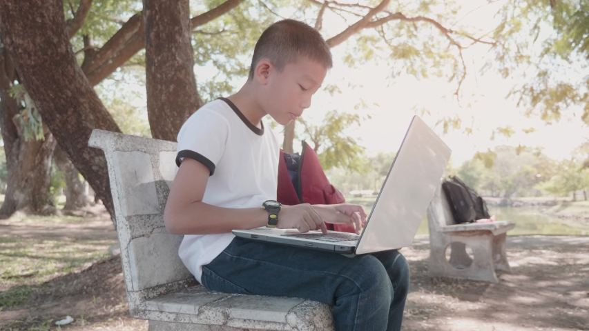 Back to School. asian boy using his laptop to learning online.  | Shutterstock HD Video #1049790766