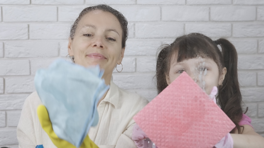 Daughter with mom wash the windows. | Shutterstock HD Video #1049978506