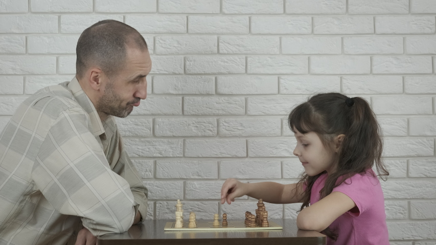 Family chess. A happy man sits by the table and play chess with his daughter. | Shutterstock HD Video #1049978536