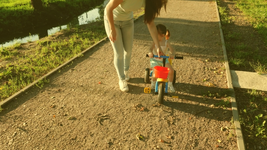 Small child learns to ride a bike by his mother. Mom teaches daughter to ride a bike in the park. Mother plays with her little daughter. The concept of a happy childhood. | Shutterstock HD Video #1049992546