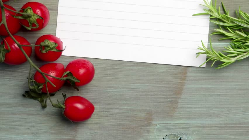 closeup of bunch of wet tomatoes and rosemary on wooden kitchen