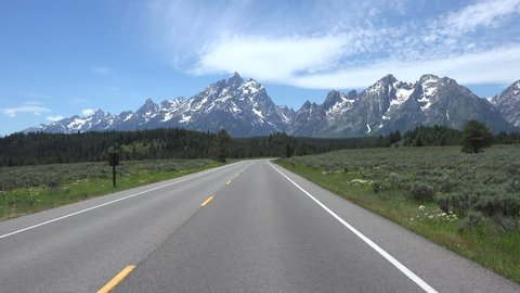 GRAND TETON, WYOMING - APR 2015:  Drive POV beautiful Grand Teton Mountain range 4K. Point of view vacation travel. South of Yellowstone. Pristine wonder and beauty. Wildlife tourism destination.