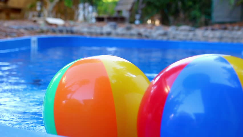Pool Water With Beach Ball colorful beach ball thrown into the water in the pool stock