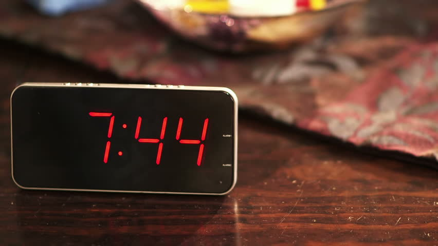 Close-up of a digital clock placed on wooden table when the time's passing. | Shutterstock HD Video #10540955
